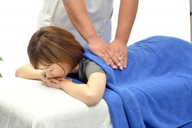 うつ伏せの女性患者に施術する整体師