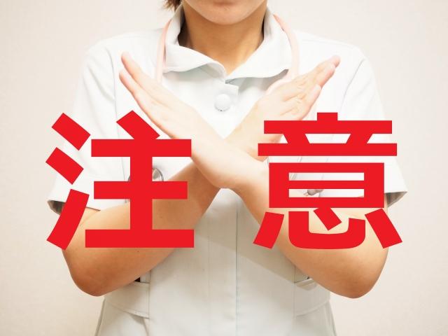 バツサインをする助産婦と注意の文字