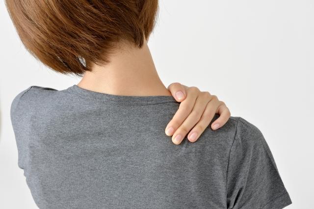後ろ向きに肩を押さえる女性