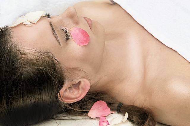 顔に花びらをのせているマッサージを受ける女性