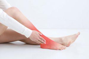 傷めた足を押さえる女性