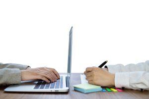 パソコン作業とメモを取る女性の手元
